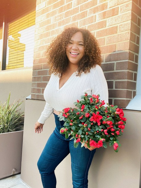 Black woman with curly hair holding flowers