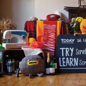 A group of crafting items such as a sewing machine, stuffed toys, a chalk board and other accouterments.