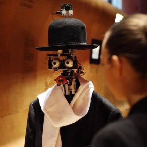 A woman stands speaking with a robot with no face but has eyes an lips wearing a top hat and scarf with a jacket.