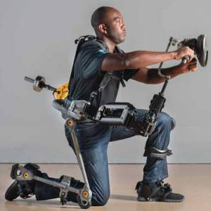 A man kneels on one knee and holds his arms out in front of him wearing an exoskeleton enabling him to do so.