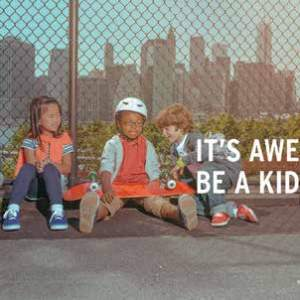 A group of children sit next to a chainlink fence wearing wristbands