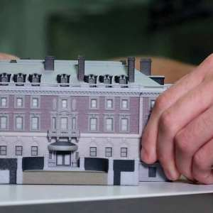 Someone's hands manipulate a miniature building