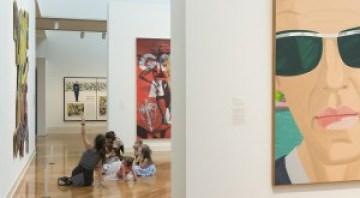 Several people sit on the floor of a gallery and look up at the art.