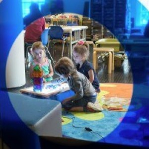 Picture taken through a blue tinted glass looking toward a group of children interacting with a light table.
