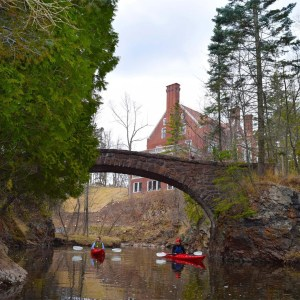 Image of two people in kayaks traveling toward the camera floating under a stone bridge with rock walls on either side, heavy plant growth to the left and Glensheen mansion visible behind them.