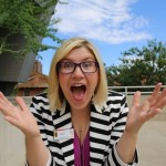 A very excited woman looks as though she is coming toward the camera with her arms close to her body but her hands wide open an expression of awe on her face, mouth open, eyes wide. She has shoulder length blond hair and she is wearing dark rimmed glasses, a black and white striped jacket and a purple top.