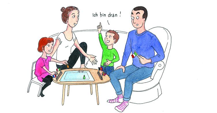 """Une famille joue à un jeu de société en allemand, le garçon s'exclamant """"ich bin dran!"""""""