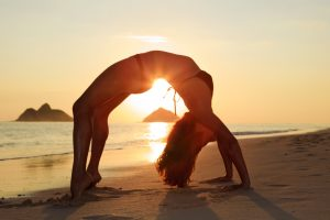 a confident girl doing beach yoga after full bikini waxing in North Jacksonville