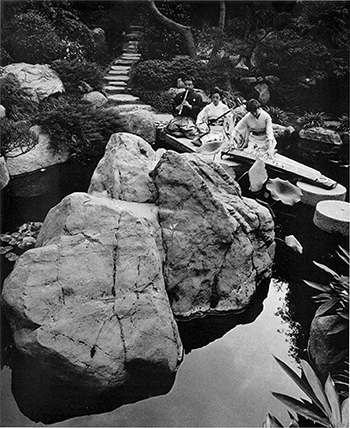 Photograph of Bonnie Wade playing the koto on the UCLA campus on a pathway over a pond.