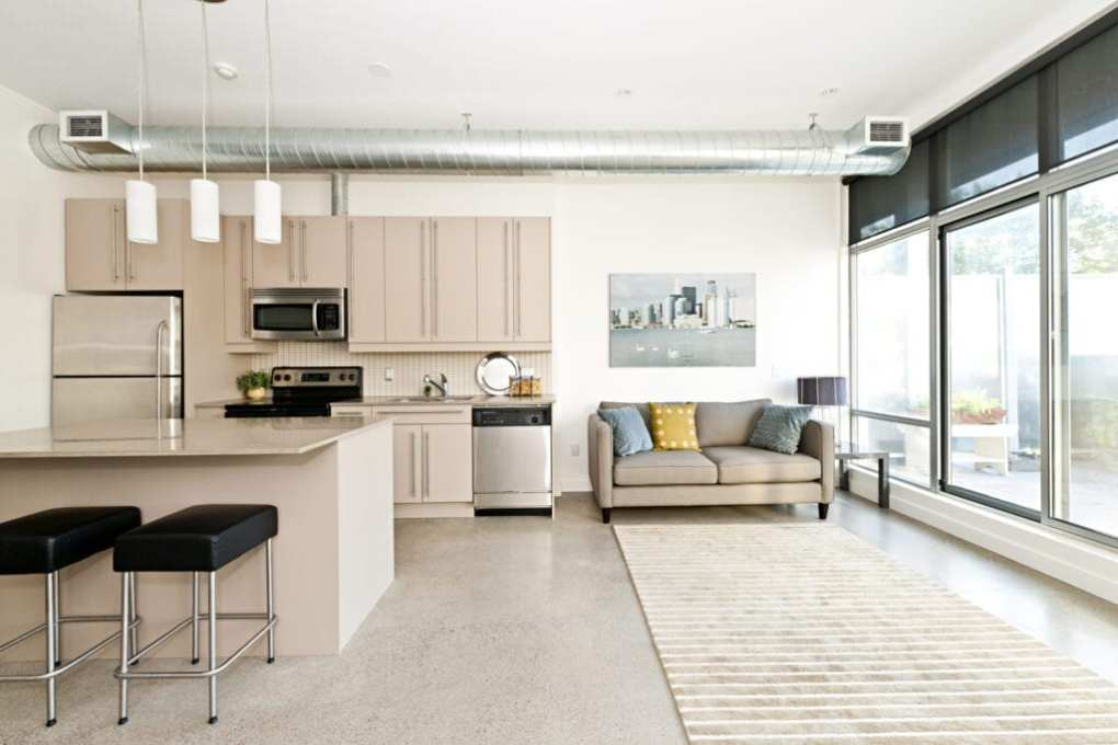 Kitchen and living room of small loft apartment, space is designed to make it look bigger