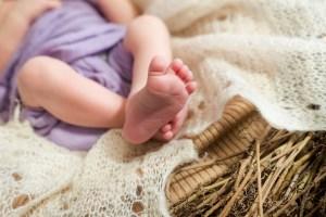Baby in Stoffwindeln und Weidenkorb