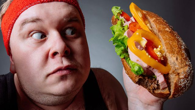 image shows an overweight man staring hungrily at a sandwich