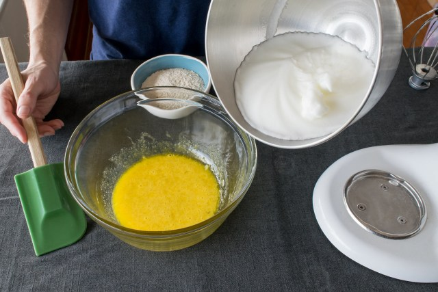 adding the fluffy egg whites to the golden yolks