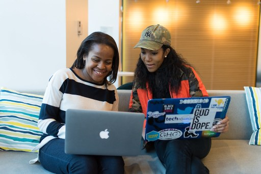 two African American females looking at laptop computer screens