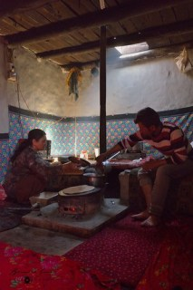 In the house of Mrs Pari Jahan. She prepares chapati on a stove in front of dildung. Kitchen is separated from the main room. © Bernard Grua