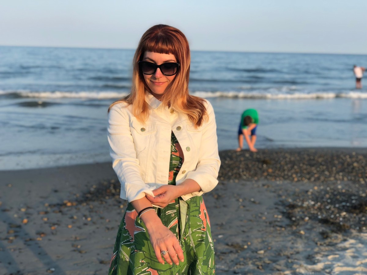 Lauren stands on a pebbled beach. She is wearing large black sunglasses, a white denim jacket and a green and peach patterned dress.
