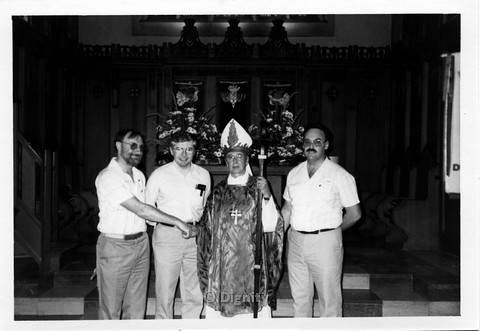 P107.004m.r.t Dignity/Canada/Dignite May 1986: Three men standing with a priest (left most shaking hands with priest)