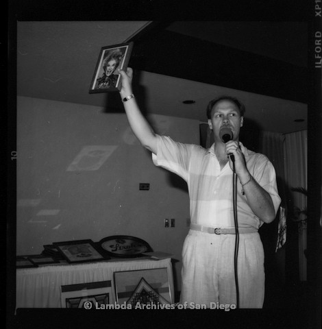 P116.115.09m.r.t San Diego Walks for Life 1987: Man talking in to microphone holding up a framed photo