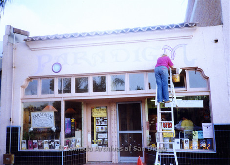 """P167.038m.r.t Paradigm Women's Bookstore: Woman on ladder painting """"M"""" in """"Paradigm"""" above store front"""