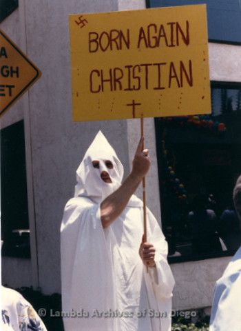 San Diego LGBTQ Pride Parade, July 1988: Protesting the Anti-Gay protesters, a man in KKK white robe with a sign labeled 'Born Again Christian' with a swastika on it