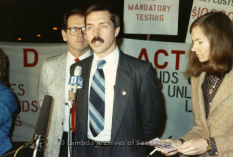 """P019.338m.r.t Los Angeles """"Die In"""" 1988:  Man speaking at channel 11 KTTV/Fox microphone, sign in background reads """"NO MANDATORY TESTING"""""""