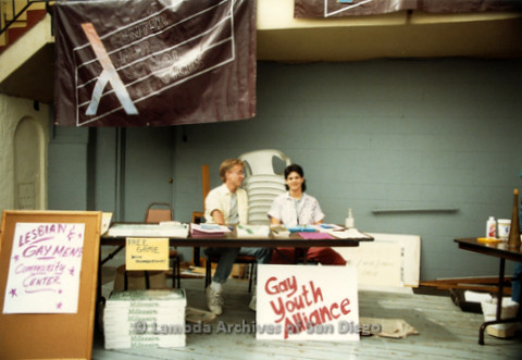 "P019.309m.r.t M.A.P. Bake Sale/Art Auction: Two men behind a table with a sign that reads: ""Gay Youth Alliance"""