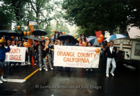 "P019.112m.r.t March on Sacramento 1988 / Parade: Group marching with a sign that reads ""National March on Washington Orange County California October 11, 1987"""