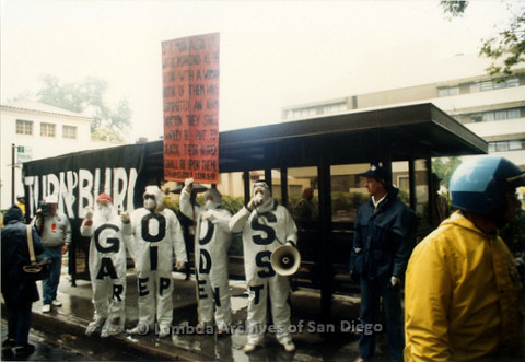 """P019.116m.r.t March on Sacramento 1988 / Pre Parade gathering: Four protesters wearing jumpsuits and masks, wearing outfits that read """"GODS AIDS REPENT""""."""