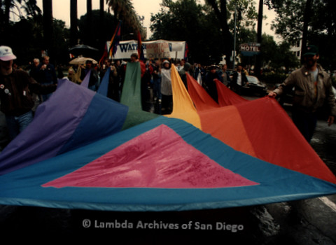 P019.390m.r.t March on Sacramento 1988: People marching while holding rainbow with pink triangle on it