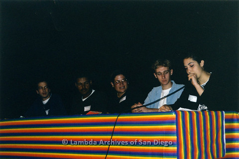 "P122.018m.r.t Youth Speak to GLSEN ""II"": Youth sitting on stage behind table with rainbow cloth, with a young woman speaking into microphone"