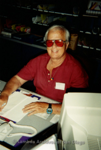 "P239.020m.r.t The Center on Normal Street: Man, ""Bobby R,"" behind desk smiling at camera and writing on paper"