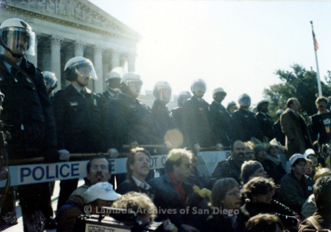 P019.220m.r.t Second March on Washington 1987: Crowd sitting beside police guarded barricade in front of U.S. Supreme Court