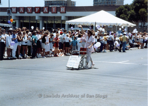 "P018.033m.r.t San Diego Pride Parade 1988: woman pushing a wheelchair with a sign on it reading: ""Honoree Grand Marshall Sharon Nowalski"""