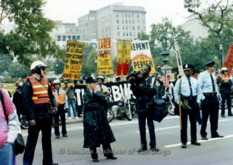 P019.223m.r.t Second March on Washington 1987: Religious protesters standing on street (background) with police officers standing in line (foreground)