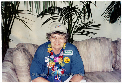 P201.002m.r.t San Diego Pride Parade 2000: Jeri Dilno sitting on a couch wearing various buttons, stickers, and necklaces