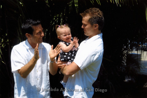 P249.001m.r.t First Same Sex Weddings in San Diego: Two men holding a baby girl outdoors