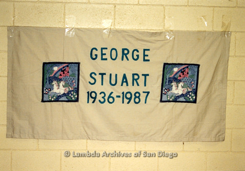 P019.058m.r.t AIDS Quilt at San Diego Golden Hall 1988: White quilt decorated with patches of resting unicorns dedicated to George Stuart