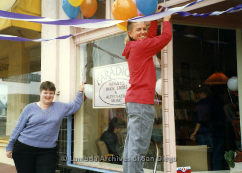 P169.100m.r.t Paradigm Women's Bookstore Grand Opening: Two women outside bookstore hanging streamers