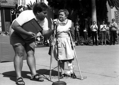 P116.038m.r.t San Diego Walks For Life 1986: Zelda Rubinstein on crutches and man by microphone