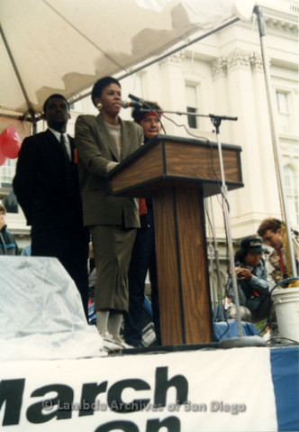 P019.159m.r.t March on Sacramento 1988 / Pre Parade gathering: Woman speaking at podium on stage in front of City Hall