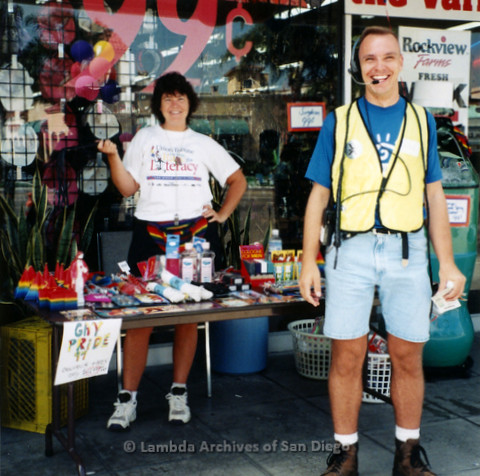 P119.067m.r.t San Diego Pride 1997: Julie Warren behind a merchandise table and George Craltree wearing a safety vest and headset