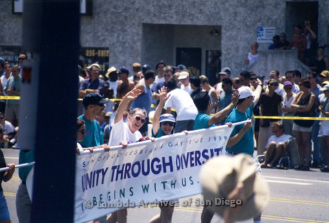 """San Diego LGBTQ Pride Parade, July 1998: Joe Mayer (left) Sheila Clark (2nd left) and Judy Reif (center) waving while carrying the 1998 parade theme banner 'Unity Through Diversity""""."""