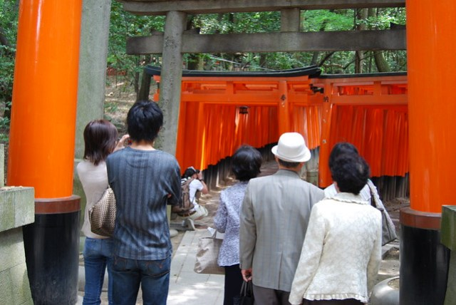 Japanese tourists practice some polite waiting while someone's taking photos