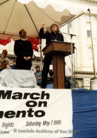 P019.174m.r.t March on Sacramento 1988 / Pre Parade gathering: Woman speaking at podium on stage with a man standing behind her, both wearing clerical collars