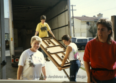 P169.037m.r.t Paradigm Women's Bookstore - Moving in: Women carrying table off moving truck