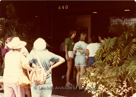 Blood Sisters blood drive, 1983: Carol Adsit speaking with guests in front of Blood Bank entrance