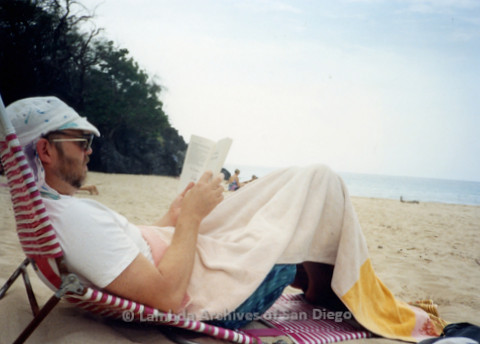 P338.006m.r.t Charles McKain sitting and reading on Hapana Beach in Hawaii