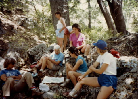 P008.048m.r.t Mt. Laguna 1983: Margaret Lewis, Diane F. Germain, and other hikers sitting on rocks and consulting a map