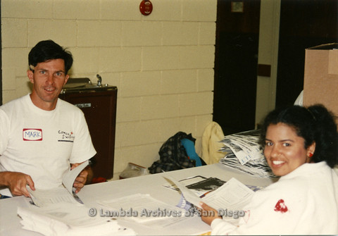 P019.021m.r.t AIDS Quilt at San Diego Golden Hall 1988: Mark and unknown woman putting together AIDS Quilt information pamphlets