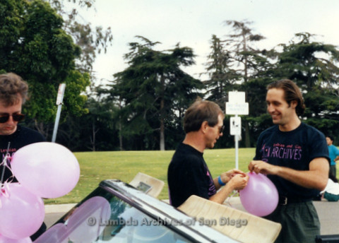 P119.023m.r.t San Diego Pride: (L-R) Andy Spurlock, John (?) and Jim Ely in Lambda Archives shirts blow up balloons around a car
